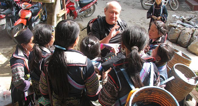 Geoff surrounded by Vietnamese women selling wares in Sapa